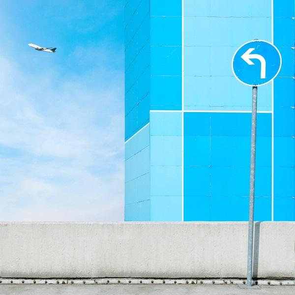 Wegweiser nach links und ein startendes Flugzeug.